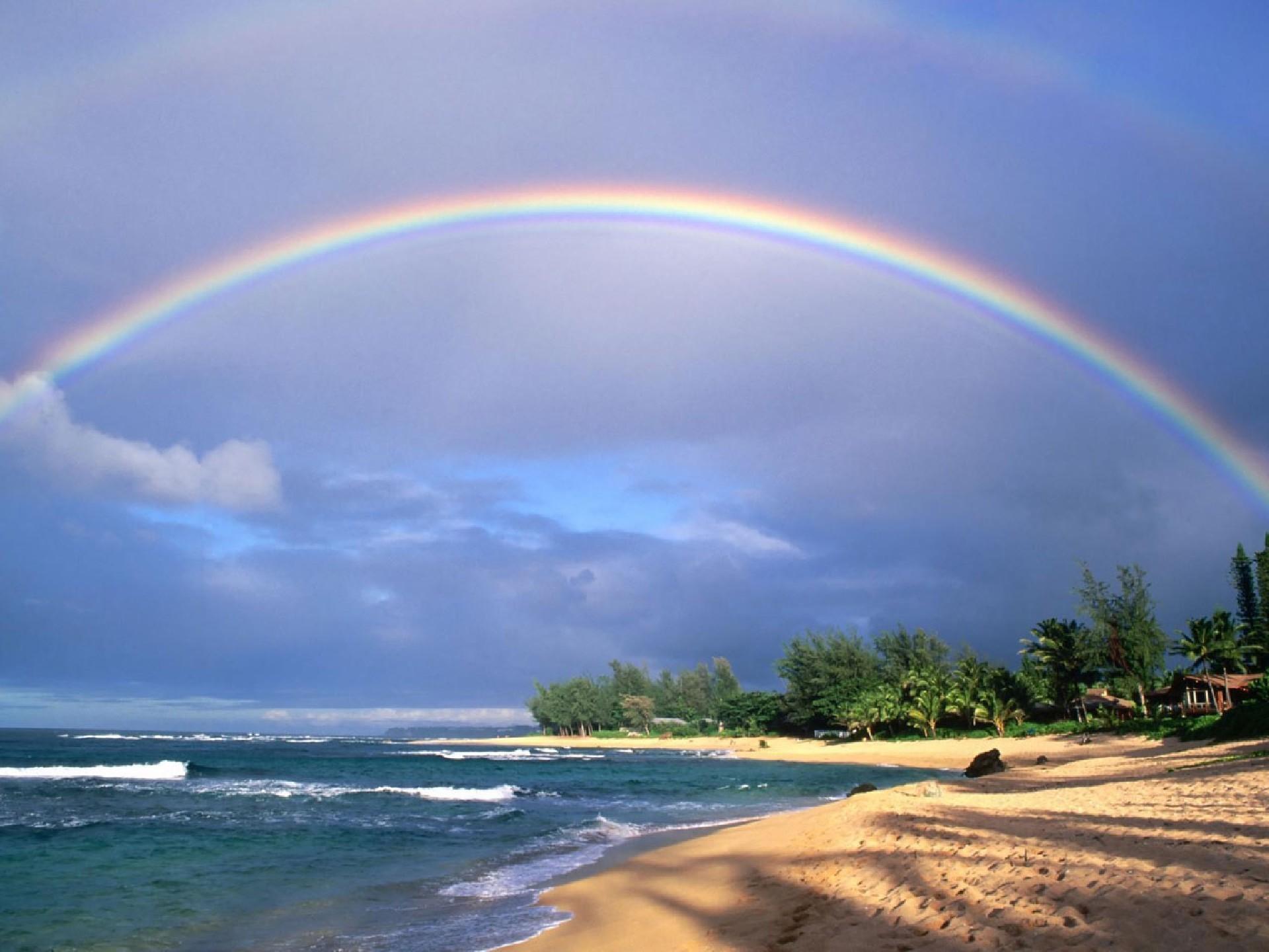Радуга на море над пляжем растянулась